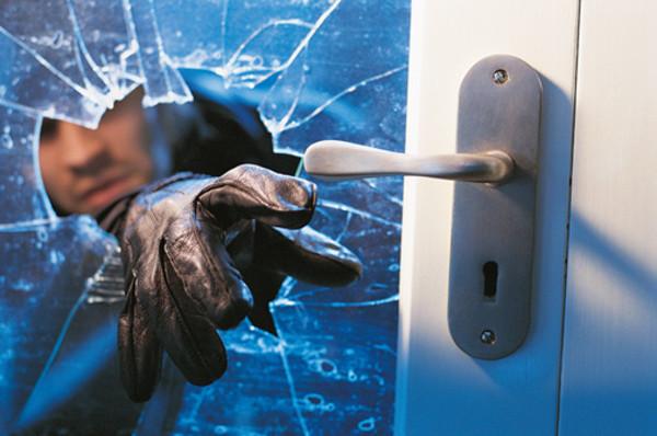 burglar reaching through broken glass in door