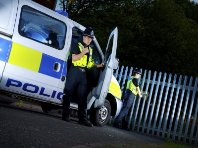 Police officers with van checking gates